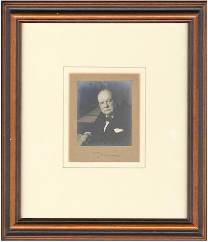 "CHURCHILL (WINSTON) Photograph signed (""WSChurchill"" on mount""), showing Churchill seated with his right arm resting on the edge of the Cabinet table, [c.1941]"