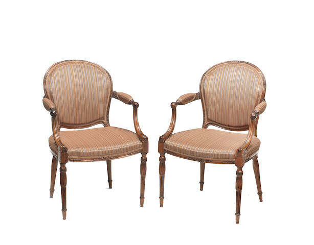A pair of George III carved mahogany open armchairs in the manner of John Linnell