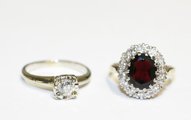 A diamond single stone ring and a garnet and diamond cluster ring,