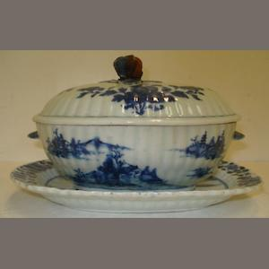 A Chinese blue and white oval sauce tureen, cover and stand, Qianlong, painted with flowers and water landscapes, the tureen 21cm, the stand, 24cm.