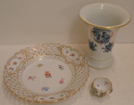A Meissen porcelain shaped circular dish, painted with scattered flowers, pierced trellis work borders, heightened with gilding, 28.5cm, painted and impressed marks, a Meissen trumpet shape vase painted with dragons and fish heightened with gilding, 19.5cm, and a small lobed circular Meissen bowl, painted with insects and encrusted with flowers. (3)
