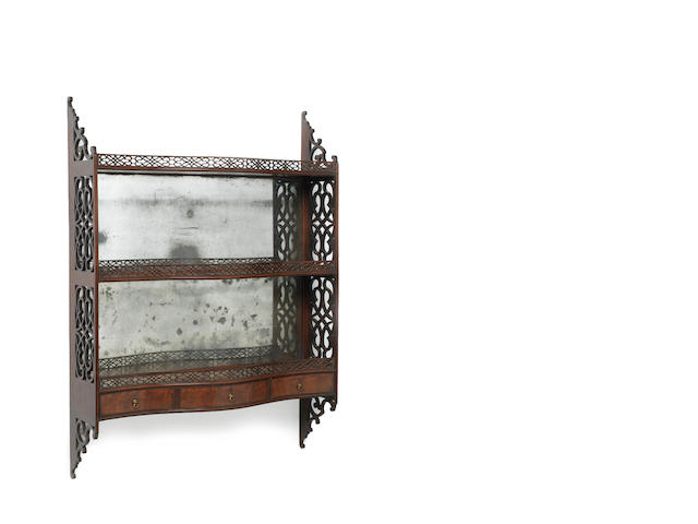 A set of mahogany serpentine hanging shelves in the Chippendale style