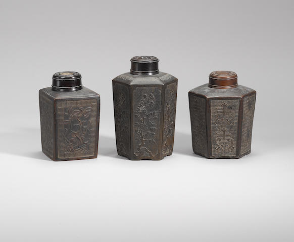 A group of three Yixing stoneware tea canisters with moulded decorations  Qing dynasty