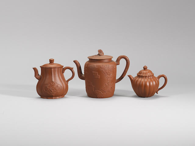 An Yixing stoneware 'appliqué-decorated' teapot and cover with two other teapots Qing dynasty