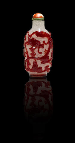 A red glass overlay 'phoenix and dragon' snuff bottle Mid Qing dynasty