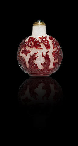 A red glass overlay 'monkey and peach' snuff bottle Mid Qing dynasty