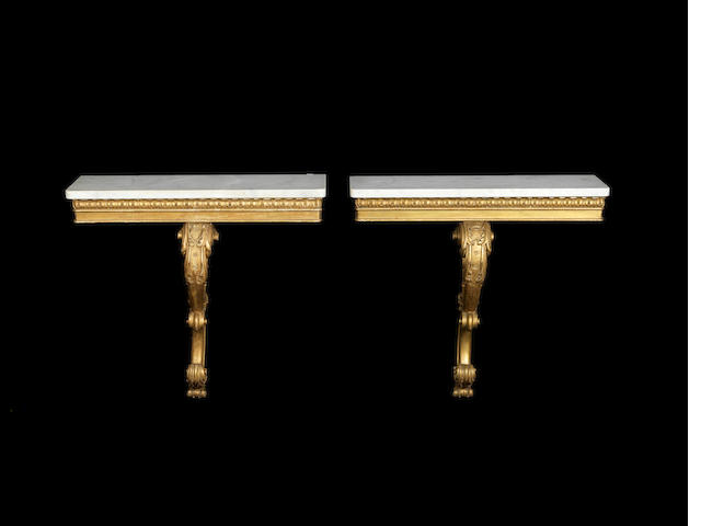 A pair of William IV carved giltwood console tables,