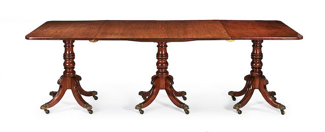 An early 20th century mahogany triple pedestal dining table in the Regency style