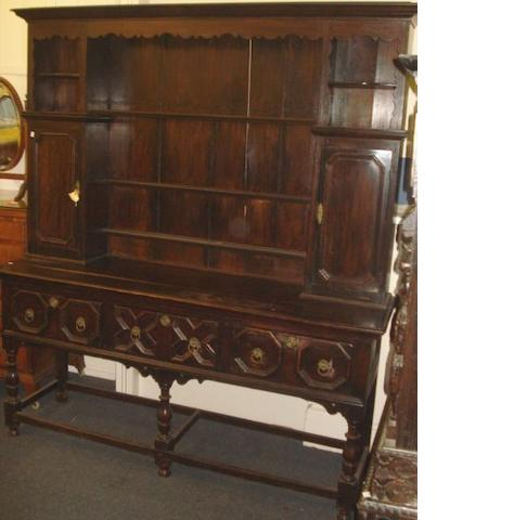 An early 20th Century dark oak dresser, in the 18th Century style, the shelved back with two small cupboard doors and pigeon holes, the projecting base fitted with drawers on turned legs untied by bar stretchers, 184cm wide, 219cm high.