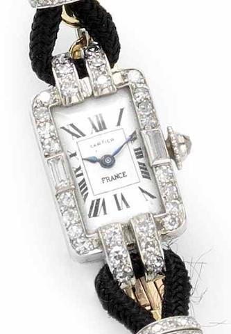 Cartier. A lady's platinum diamond set manual wind wristwatch