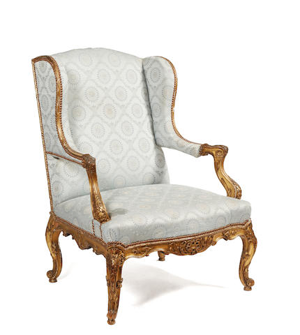 A late 19th century Louis XV style carved giltwood and gilt gesso wing chair