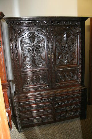 An 18th century oak and later carved press cupboard