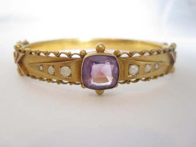 An early 20th century 9ct gold amethyst and seed pearl bangle