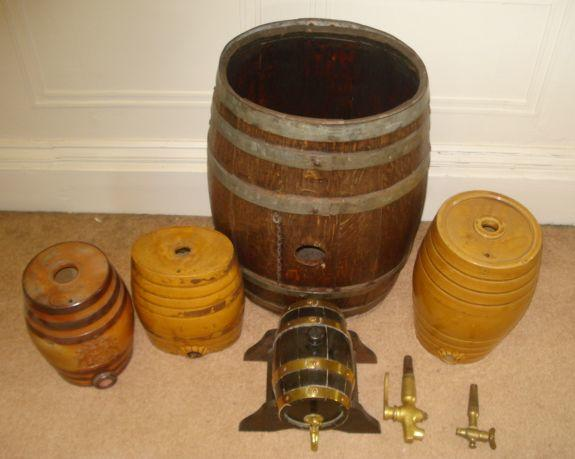 A coopered oak oval sped barrel, 58cm, a Doulton and Watts salt-glazed 'Brandy' barrel, 23cm, two other glazed barrels, another on stand and two brass spigot taps.