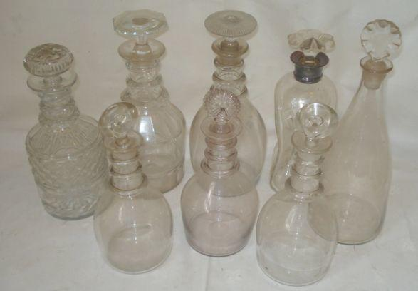 A pair of early 19th Century blown glass mallet shaped decanters, with triple ring necks and bulls eye stoppers, 23cm, another with different stopper and four other later cut and plain decanters. (7)