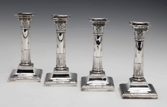 An Edwardian set of four silver candlesticks  by H Eyre, Sheffield 1902