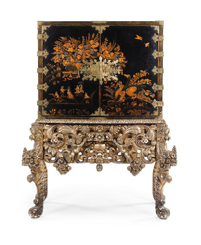 A black and gilt japanned cabinet on a carved, silver-gesso stand