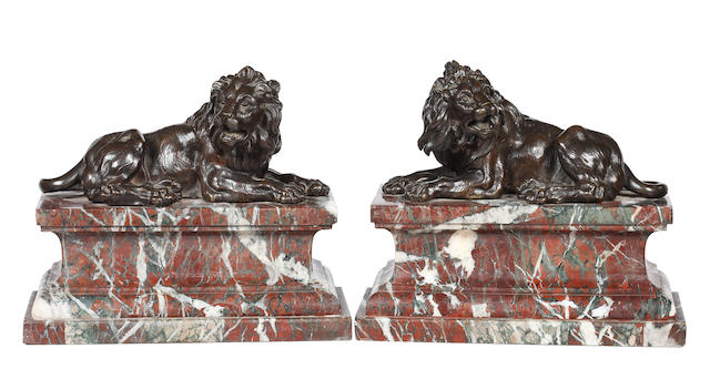 A pair of bronze recumbent roaring lions