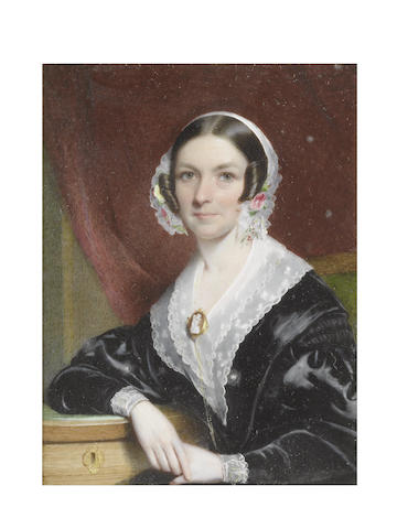 Sir William Charles Ross (British, 1794-1860) A Lady, seated on a green upholstered chair and wearing black dress, white lace collar and cuffs, gold mounted cameo brooch fastened to her corsage with falling gold chain, her white lace bonnet dressed with flowers, her right arm resting on a green covered writing desk