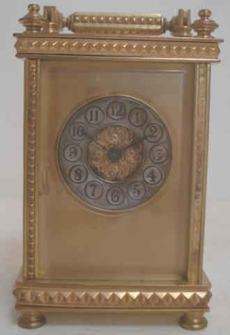 A Victorian brass carriage timepiece, with lever platform escapement, circular silvered dial with Arabic numerals within a gilt mask, with key, 15cm.