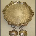 A Victorian shaped circular silver waiter, R&H, Sheffield 1848, with moulded rim, foliate and 'C' scroll engraved centre, on pierced scroll feet, 17cm, and a pair of George III canted corner rectangular Brandy & Whisky labels, Joseph Willmore, Birmingham 1811, 7ozs. (3)