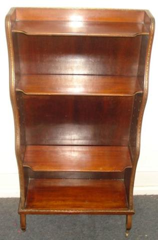 A Regency style mahogany gilt metal mounted dwarf waterfall bookcase, circa 1900, with open adjustable shelves, on scrolled legs and castors, 48cm.