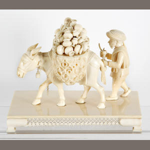 An Indian ivory carving Of a pedlar walking behind his mule, fully laden with pots