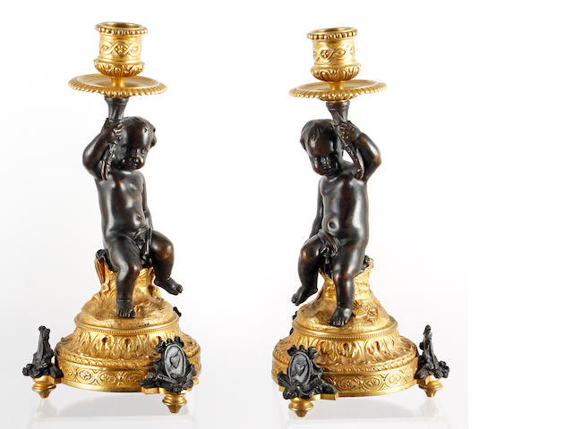 A pair of late 19th Century French gilt metal and bronze candlesticks