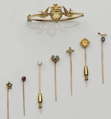 A seed pearl and citrine bangleThe central heart motif between two love birds, with ribbon bow surmount, centrally set with a heart-shaped citrine to borders of graduated seed pearls, together with a diamond single stone stick pin, claw set with an old-cut diamond, (later adapted), a ruby single-stone stick pin, collet set with an oval mixed-cut stone, (later adapted), and five others, bangle inner diameter 5.7cm. (8)
