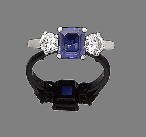 A sapphire and diamond ring, by Cartier The step-cut sapphire, between two brilliant-cut diamonds, diamonds approx. 0.60ct total, signed Cartier, ring size I½ (sizing beads), maker's case