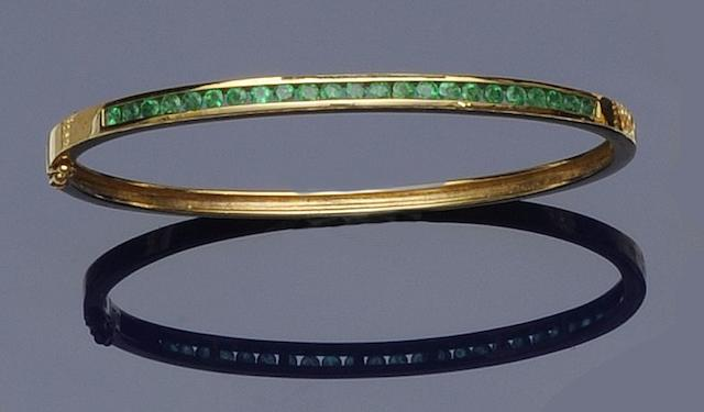 An emerald set hinged bangle