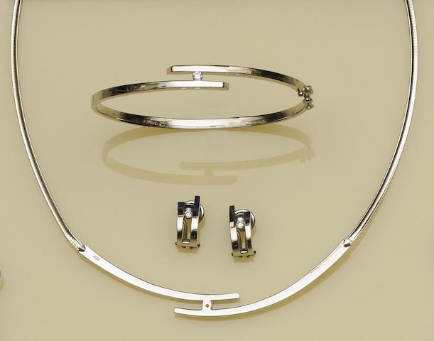 An 18ct white gold necklace, bangle and earclips suite