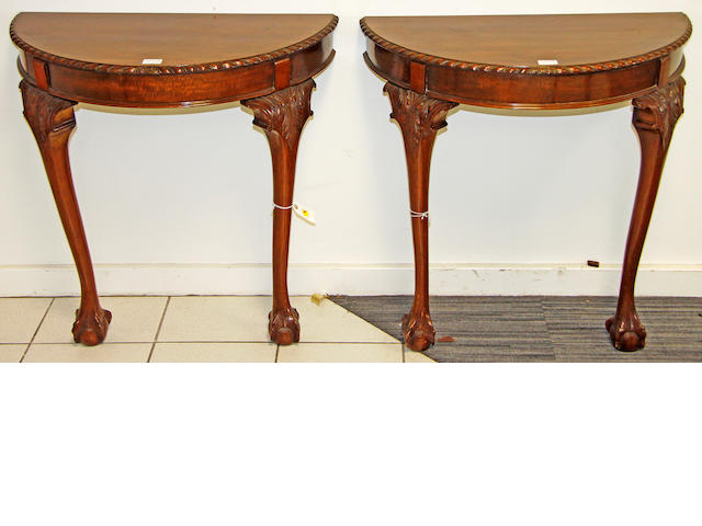 A pair of mahogany demi-lune console tables,