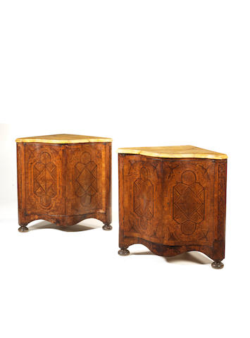 A pair of Italian 18th century walnut, fruitwood and parquetry serpentine corner cabinetswith later restorations