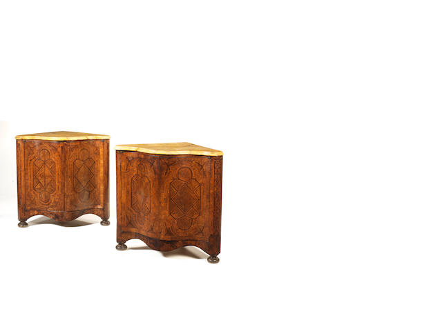 A pair of Italian 18th century walnut, fruitwood and parquetry serpentine corner cabinets with later restorations