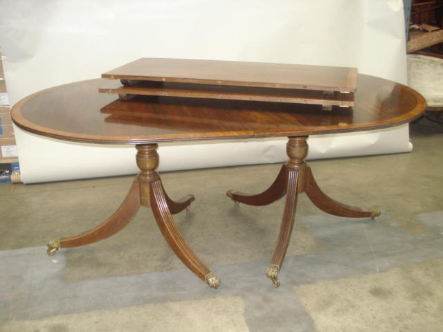 A reproduction Regency style mahogany and banded twin pillar dining table