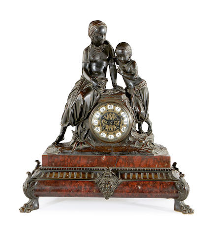 A late 19th century French bronze and Rouge Griotte marble figural mantel clock