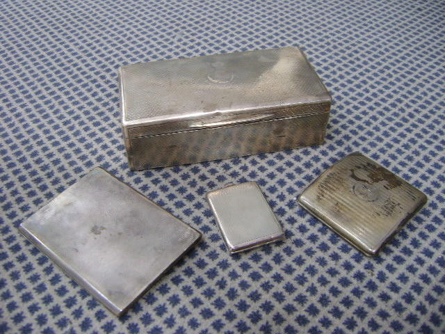A silver cigarette box, engine turned, two cigarette cases and a match case, all silver weighable weight 11oz. (4)
