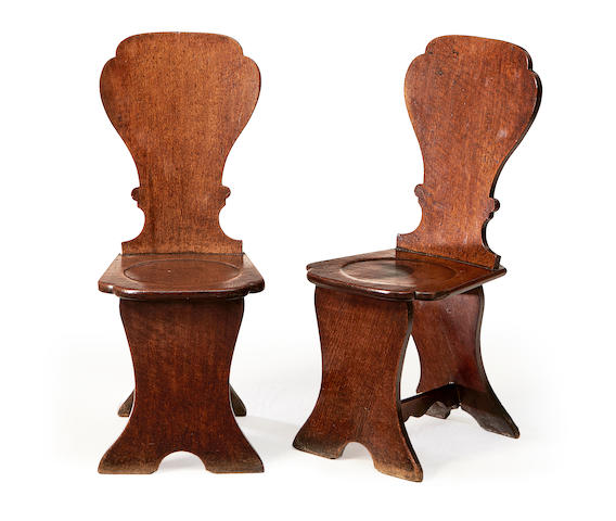 A pair of George III oak hall chairs