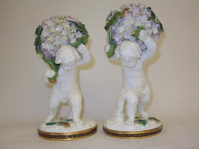 A pair of late 19th century cherub candlesticks