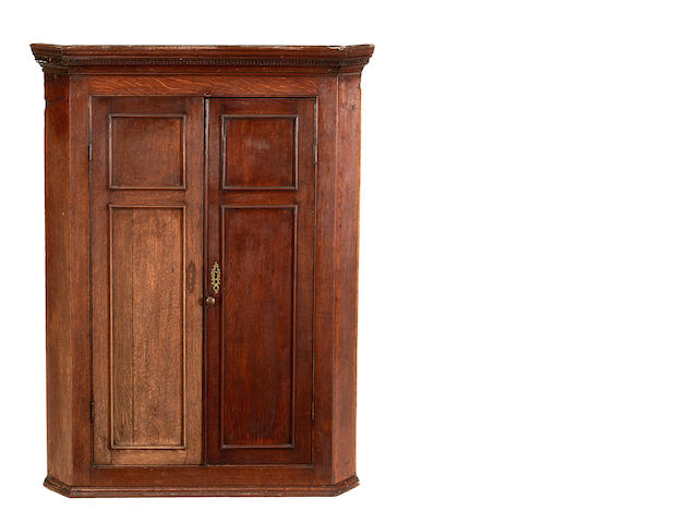 A George III oak hanging corner cupboard