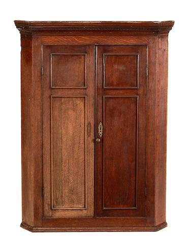 A George III oak hanging corner cupboard