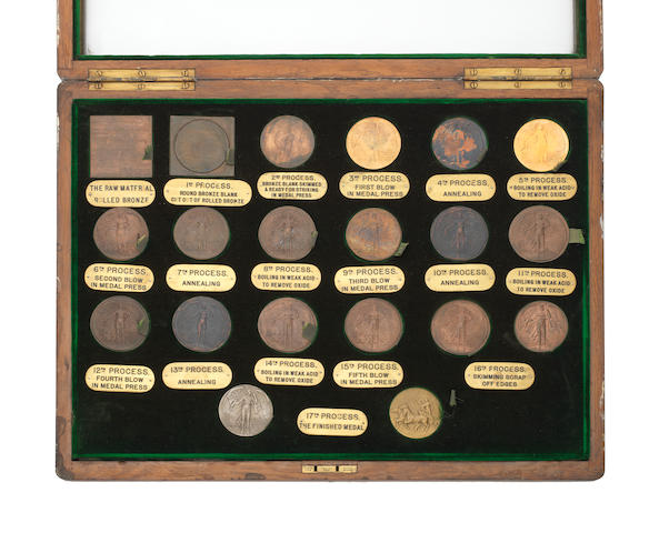 A set of Manufacturer's Production Specimens for the 1908 Olympics Participant's Medal, an extremely scarce set of 20 medals/specimens housed in a display frame from the original blank piece of metal (bronze)to the finished medal, each with a brass engraved plaque below each medal describing the manufacturing process. Housed in a contemporary oak frame, 39cm by 52cm.