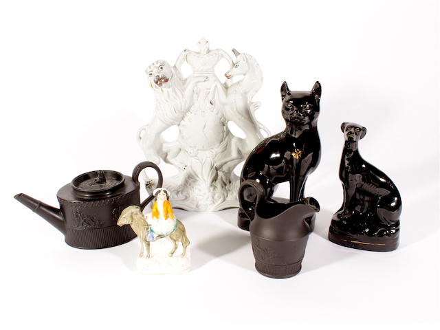 A black basalt oval teapot and cover and a cream jug, two Jackfield type animal models, a Staffordshire Royal Coat of Arms clockface and a small model of a girl on a donkey, mid-late 19th century