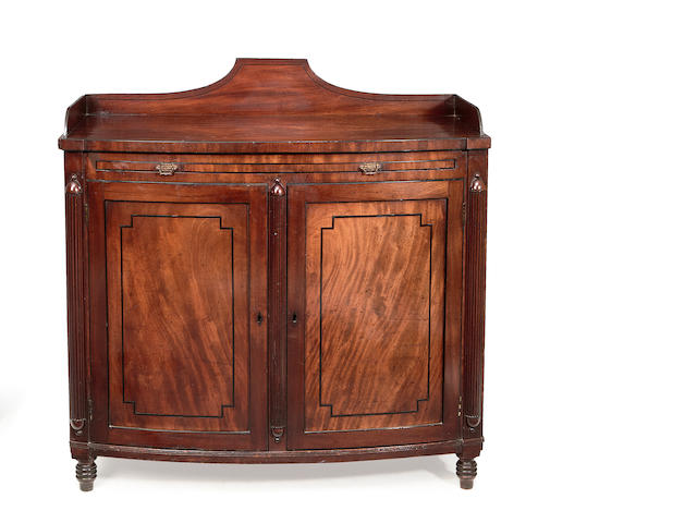 A Regency mahogany and ebonised line inlaid bowfront serving cupboard