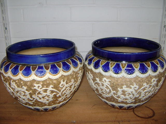 A pair of Royal Doulton jardiniers, the swelling sides with foliate bands on a buff scroll ground, 23cm diameter
