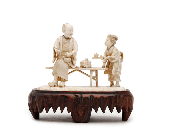 Ivory (to be confirmed) carving of male and female oriental figures on wooden base