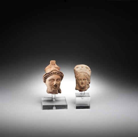 Two terracotta heads, one of Athena, 4in (10cm), another of a goddess, 3in (7.6cm) 2