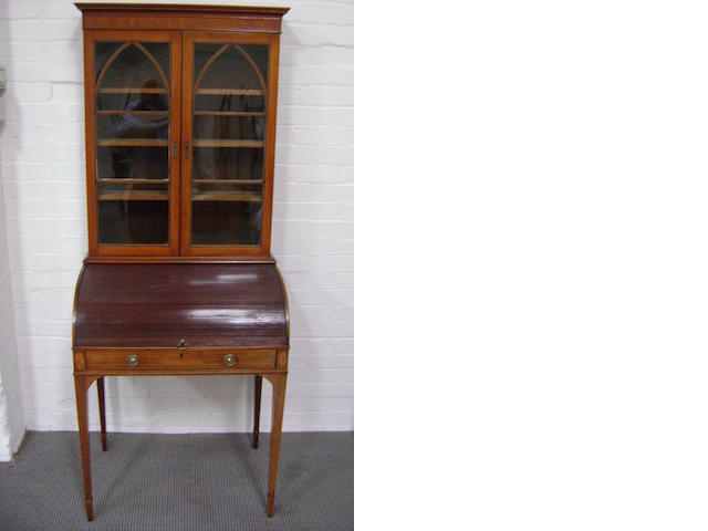 A George III mahogany Secretaire bookcase, with Gothic arch astrugals and tambour enclosed writing fitting above an apron drawer and tapered square legs. 74cm wide, 183cm high