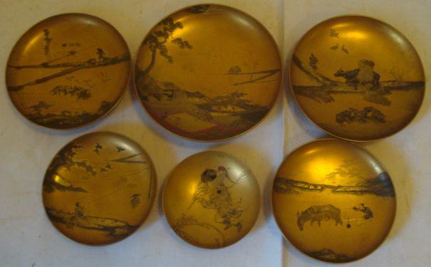 a suite of six Japanese lacqauer circular dishes, each on small circular foot, well decorated with different techniques, four depicting rice planting, harvesting and thrashing, and other subjects, all on a matt gilt ground,8.5cm to 14.5cm.